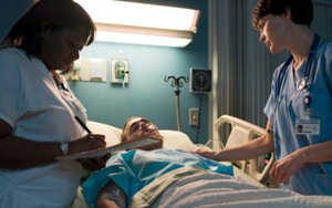 A patient in a coma flanked by nurses