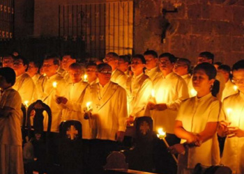 A group of parishioners holding candles to renew their baptismal promises