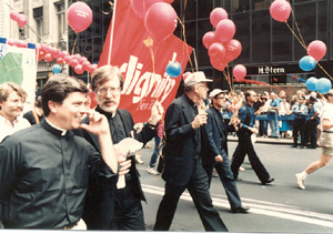 Priests in a gay parade with a cross